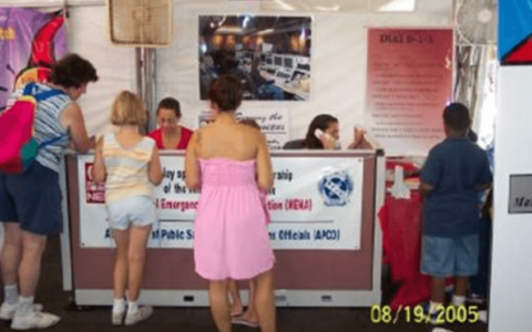 Outreach team members Denise and Terri presenting 9-1-1 education materials at the Illinois Fire Marshall's tent at the Illinois State Fair in August 2005